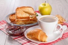 Xícara de café e croissant nos pires, bacia de vidro com strawberr Imagens de Stock Royalty Free