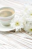 Xícara de café e flores na tabela de madeira clara Imagens de Stock Royalty Free