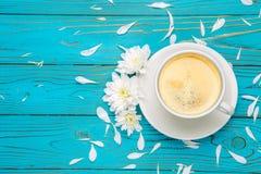 Xícara de café e flores na tabela de madeira clara Imagem de Stock