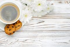 Xícara de café e flores na tabela de madeira clara Fotografia de Stock
