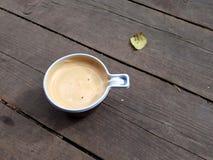 A xícara de café e o outono folheiam na plataforma de madeira imagem de stock
