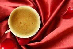 Xícara de café e pétalas cor-de-rosa na seda vermelha dobrada Fotografia de Stock