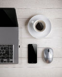 Xícara de café e portátil, rato do computador, telefone em uma tabela Imagem de Stock