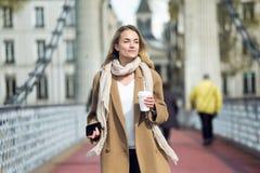 X?cara de caf? e smartphone bonitos da terra arrendada da jovem mulher ao andar na rua foto de stock