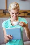Xícara de café e tablet pc guardando louros bonitos da utilização Imagens de Stock Royalty Free