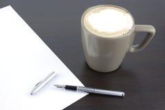 Xícara de café e uma pena na tabela do escritório foto de stock royalty free