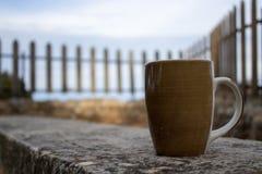 xícara de café em um banco em um mornng bonito do outono fotos de stock royalty free