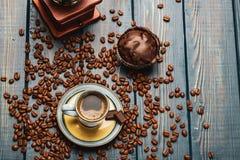 Xícara de café em uma tabela de madeira azul com feijões de café e um chocolate fotos de stock