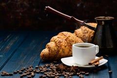 Xícara de café em uma tabela de madeira azul com feijões de café e um croissant fotos de stock