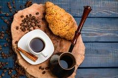 Xícara de café em uma tabela de madeira azul com feijões de café e um croissant imagens de stock