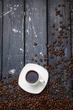 Xícara de café em uma tabela de madeira preta com feijões de café imagens de stock