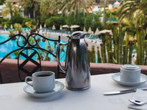 Xícara de café em uma tabela no terraço do hotel, sobre a parte traseira da associação fotografia de stock royalty free
