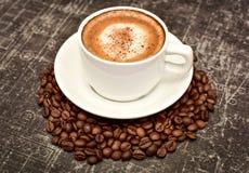 A xícara de café está estando em uma pilha de feijões de café Fotografia de Stock