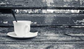 A xícara de café está no banco de madeira, monocromático Fotografia de Stock
