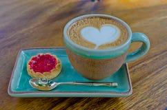 Xícara de café, forma do coração com o biscoito da morango no backg de madeira Imagens de Stock Royalty Free