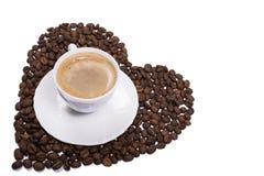 A xícara de café isolada em feijões dispersou na forma do coração fotos de stock