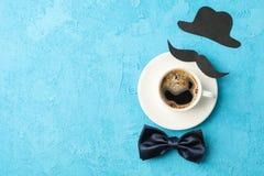 Xícara de café, laço, bigode decorativo e chapéu no fundo azul, espaço para o texto fotografia de stock