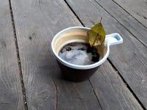 A xícara de café na plataforma de madeira com folha do outono para dentro fotografia de stock