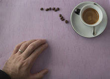 Xícara de café na tabela com mão e feijões fotografia de stock royalty free