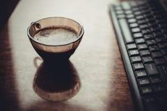 Xícara de café na tabela perto do teclado Fotos de Stock