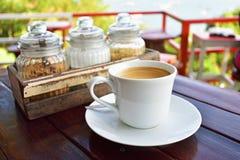 A xícara de café na tabela sobre montanhas ajardina com luz solar Fotos de Stock Royalty Free