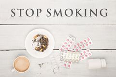 A xícara de café, os cigarros, as garrafas e os comprimidos médicos e o texto param de fumar foto de stock royalty free