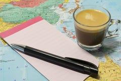 Xícara de café, pena e papel para cartas em um mapa Imagens de Stock