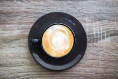 Xícara de café preta com a espuma do leite tão deliciosa na tabela de madeira velha Vista superior fotografia de stock royalty free