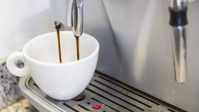 Xícara de café que enche-se em uma máquina Foto de Stock Royalty Free
