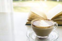 xícara de café quente com o livro no balcão da janela fora com GR fotografia de stock