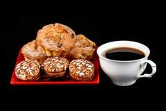 Xícara de café, queques e cookies dos pedaços de chocolate em uma placa vermelha Fotos de Stock
