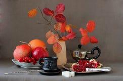A xícara de café, romã dividiu-se em partes e em folhas de outono em um vaso imagens de stock