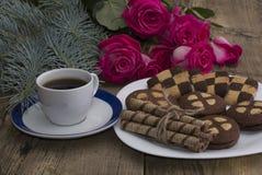 Xícara de café, rosas e placa com cookies diferentes em uma tabela Fotos de Stock