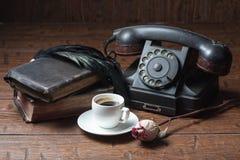 A xícara de café, seca o telefone cor-de-rosa e velho Fotografia de Stock Royalty Free