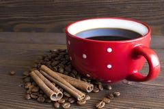 A xícara de café vermelha do às bolinhas está ao lado dos feijões de café Foto de Stock