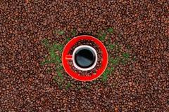 Xícara de café vermelha em feijões de café fotografia de stock