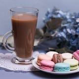 Xícara de café de vidro da manhã do close-up com leite, macaron do bolo e flor na tabela azul Sobremesa bonita foto de stock