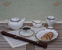 Xícara de chá inglesa com pires, bule, jarro do creme, açucareiro, uma bacia do bolo e uma flauta do bloco em uma folha da música imagem de stock