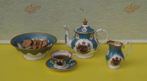 Xícara de chá inglesa com pires, bule, jarro do creme e uma bacia com cookies, porcelana fina do bolo da porcelana de osso imagem de stock