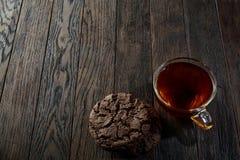 Xícara de chá de vidro com as cookies dos pedaços de chocolate no guardanapo em um fundo de madeira rústico, vista superior do al Fotografia de Stock Royalty Free