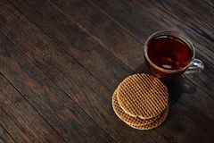 Xícara de chá de vidro com as cookies dos pedaços de chocolate no guardanapo em um fundo de madeira rústico, vista superior do al Fotos de Stock
