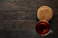 Xícara de chá de vidro com as cookies dos pedaços de chocolate no guardanapo em um fundo de madeira rústico, vista superior do al Foto de Stock Royalty Free