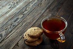 Xícara de chá de vidro com as cookies dos pedaços de chocolate no guardanapo em um fundo de madeira rústico, vista superior do al Imagem de Stock