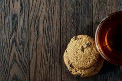Xícara de chá de vidro com as cookies dos pedaços de chocolate no guardanapo em um fundo de madeira rústico, vista superior do al Fotos de Stock Royalty Free