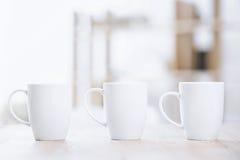 Xícaras de café brancas que estão na tabela Foto de Stock Royalty Free