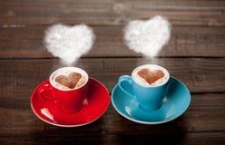 Xícaras de café de duas cores com vapores da forma do coração Imagens de Stock Royalty Free