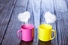 Xícaras de café de duas cores com vapores da forma do coração Foto de Stock Royalty Free