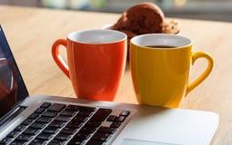 Xícaras de café e um portátil imagem de stock royalty free