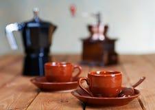 Xícaras de café e um potenciômetro do café em uma tabela Foto de Stock