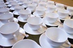 Xícaras de chá vazias empilhadas com colheres de chá em uma função sobre os vagabundos brancos Fotografia de Stock Royalty Free